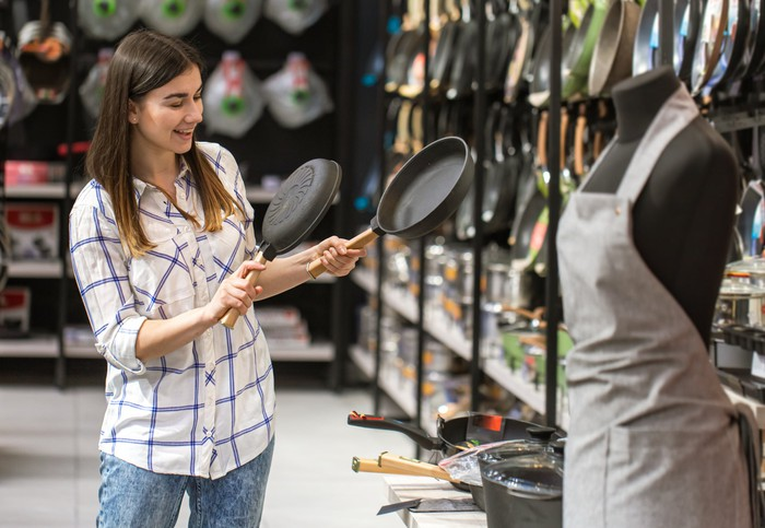 A woman comparing pans in a store.