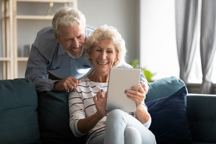 Happy retired couple smiling at a tablet.
