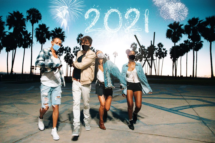 Four people celebrating in front of a background of fireworks, palm trees, and the number 2021.