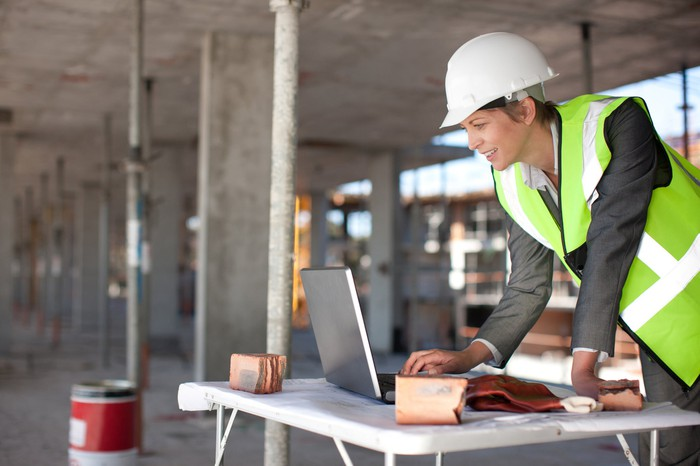 A person using a computer on a construction site.