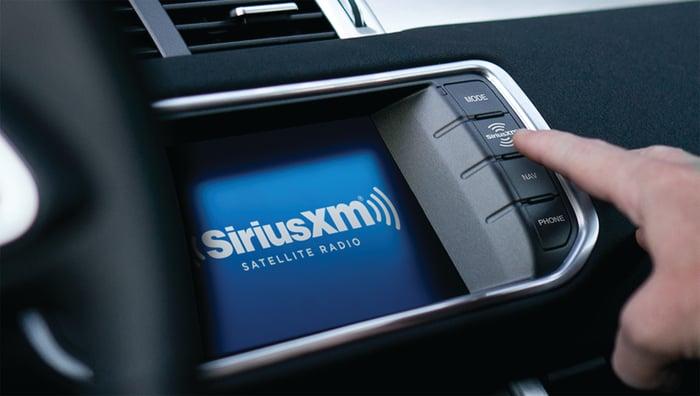 A finger pressing a button on a Sirius XM in-car dashboard.
