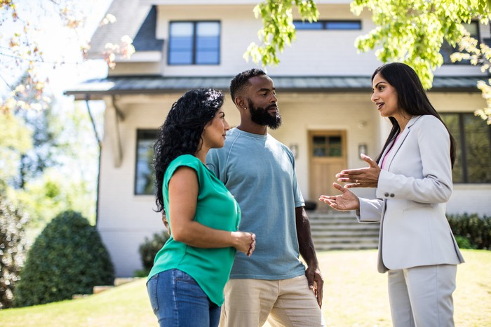 A couple talks with a real estate agent in front of a house.