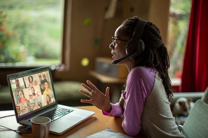 A person at a table wearing headphones with a mouthpiece videoconferencing.