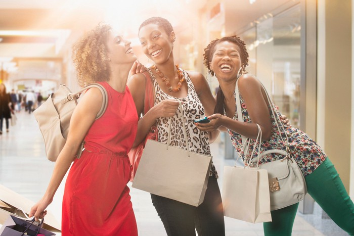 Three women at a shopping center holding shopping bags and smiling.