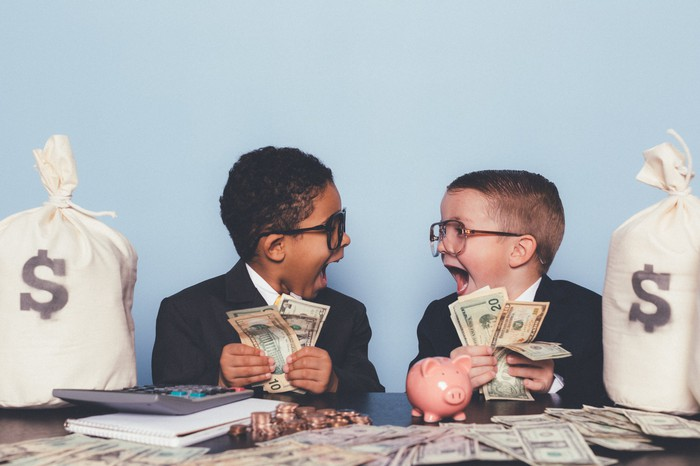 Two happy kids play with piles of cash.