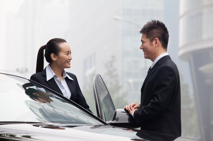 Two people stand near a car.