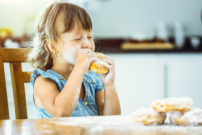 Child eating donut somewhat messily.