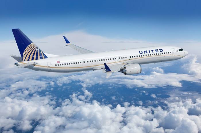A United Airlines Boeing 737 MAX 9 flying over clouds.
