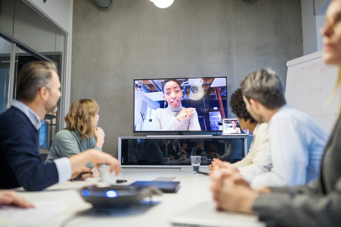Businesspeople in meeting with virtual participant.