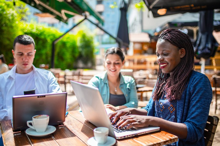 Three people working on laptops at an outdoor cafe.