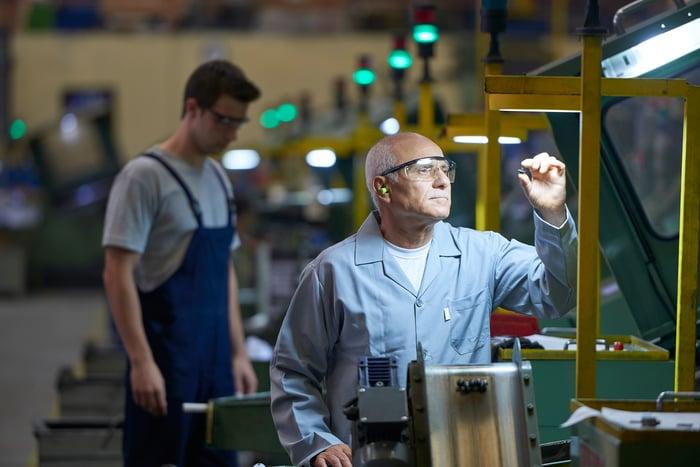 A factory employee inspects a small part under a work light