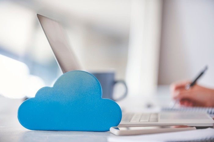 A laptop sitting on a desk with a blue cloud icon sitting next to it.