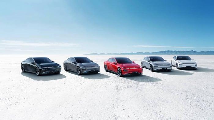 A lineup of five XPeng vehicles in a barren desert.