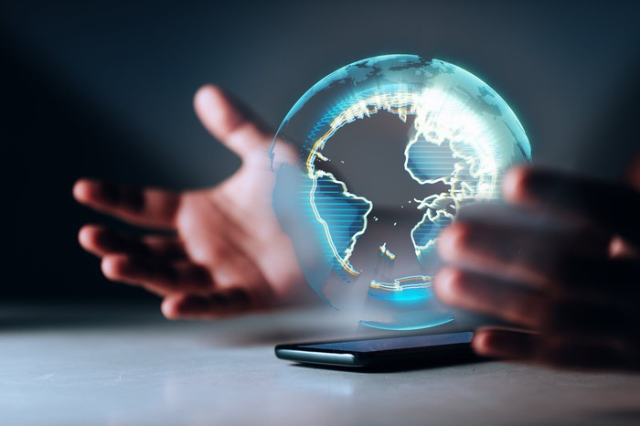 A person's hands and a mobile device displaying a globe.
