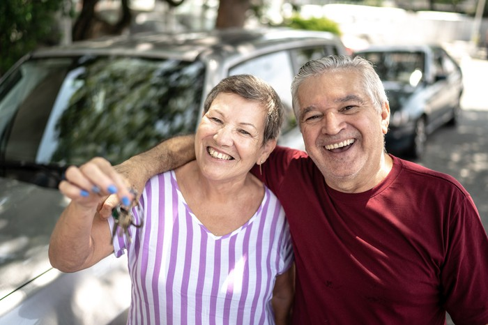 A couple holding up the keys to their car and smiling.