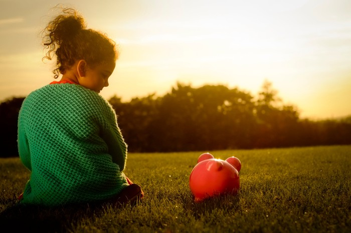 A girl looks down at her piggy bank while the sun sets in the background.
