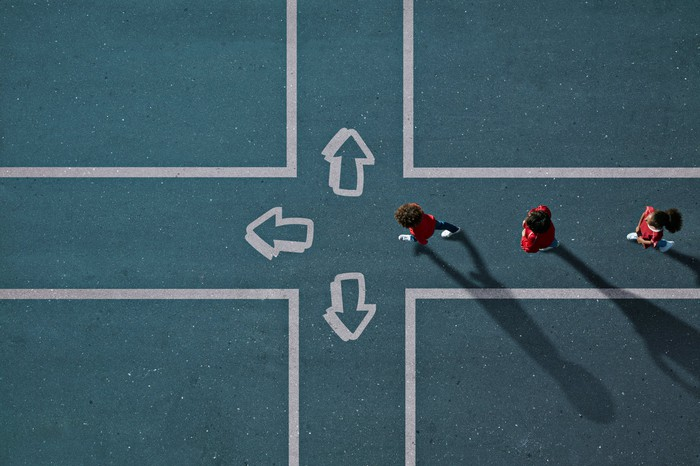 Three people approach a crossroads with three different paths