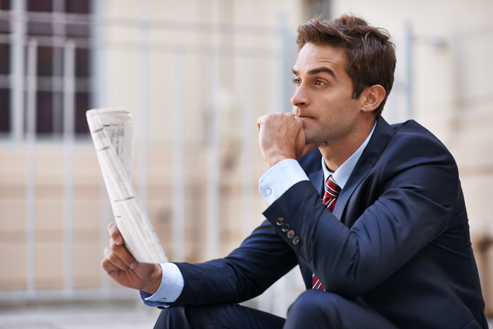 Investor holding newspaper and looking contemplative.