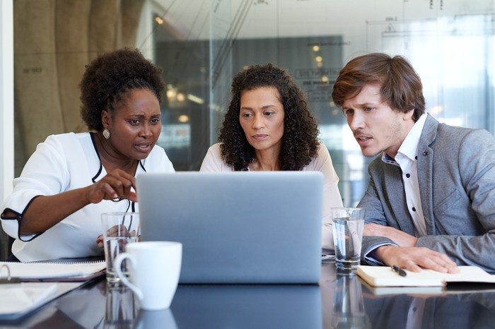 Three people with concerned expressions looking at a laptop.