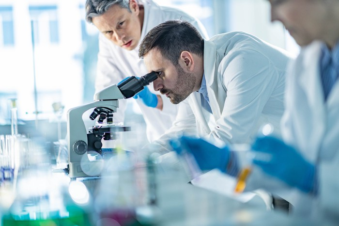 Two men in lab coats look into microscope.