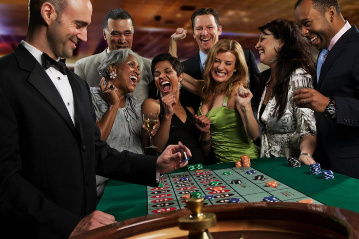 A group of folks at the roulette table.
