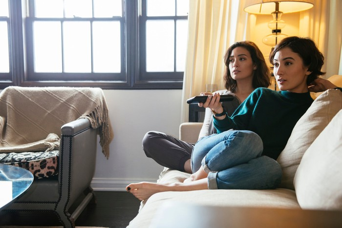 Two women sitting on a couch, one holding a TV remote.