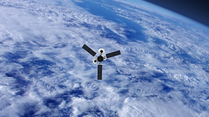 A satellite in orbit over a cloudy earth.