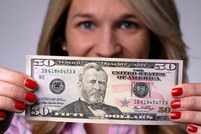 A person holding a $50 bill.