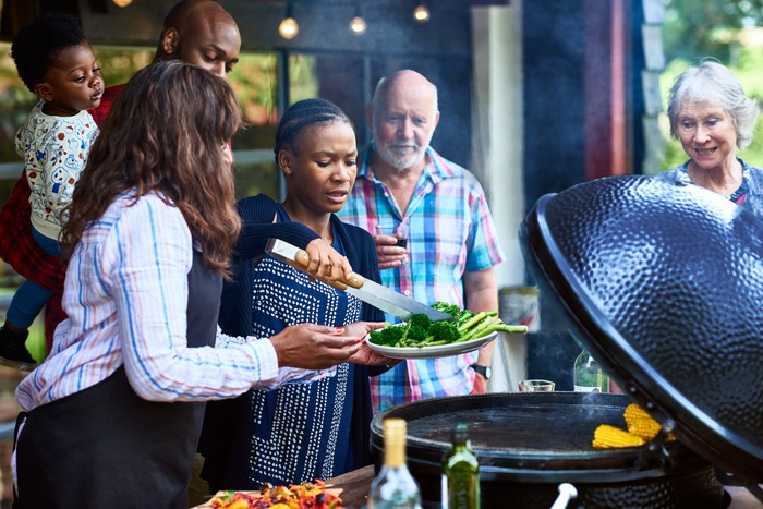 A group of people cooking and serving food off a grill.