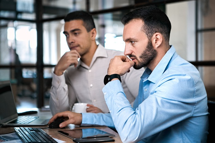 Two investors look pensive as they sit side by side at their computers.