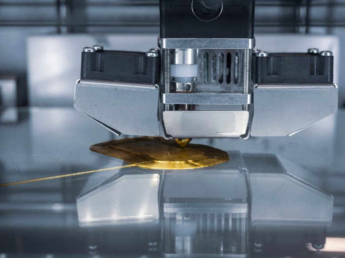 Close-up of a 3D printer in early stage of producing a gold-colored object.
