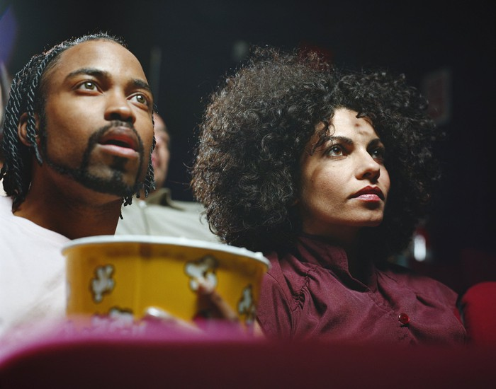 A pair of moviegoers at a movie theater with a bucket of popcorn.