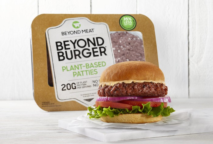 A grilled Beyond Meat burger sits on a serving tray in front of a package containing uncooked Beyond Meat burgers.