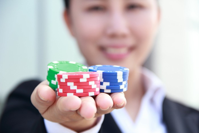 Person holding casino chips.