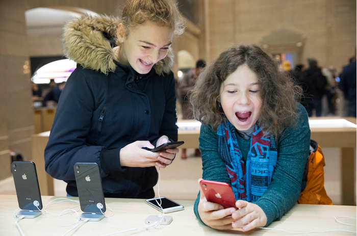 Two excited children playing with new iPhones on display in an Apple store.