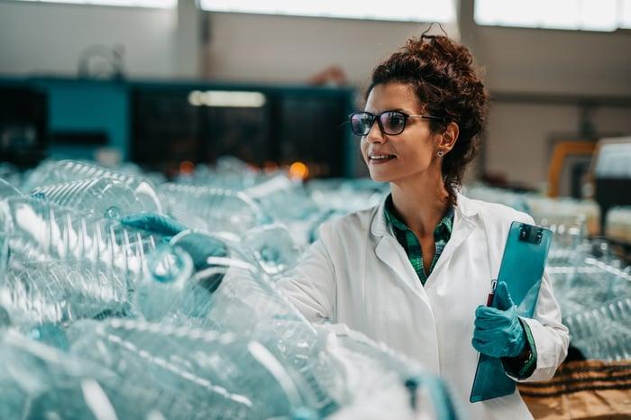 A scientist inspecting plastic bottles