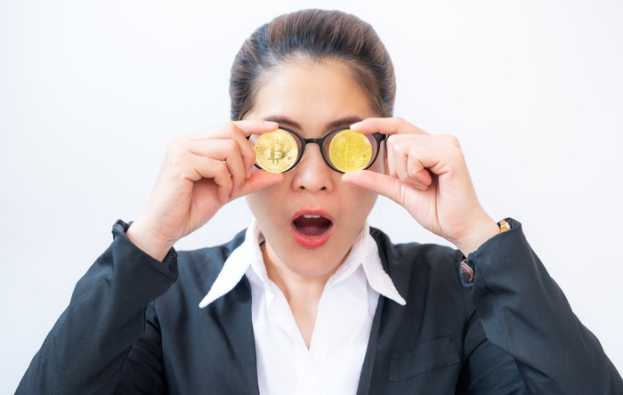 Person holding two gold-colored coins with Bitcoin symbol in front of eyeglasses.