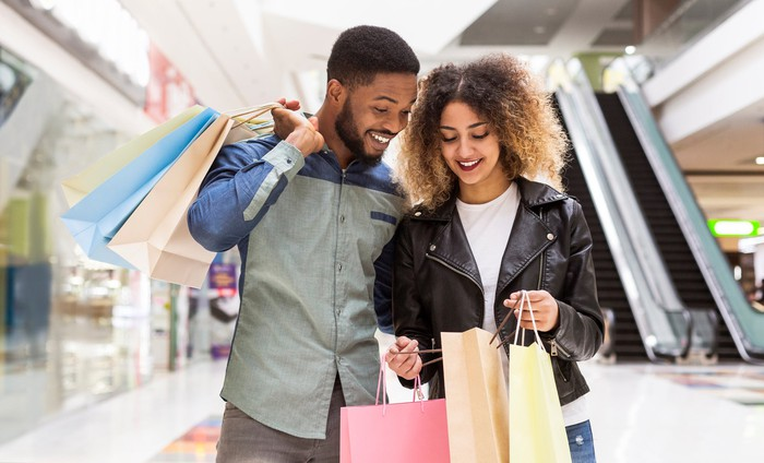 Two smiling people with shopping bags standing in a mall.