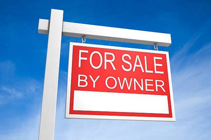 For Sale by Owner sign against a bright, blue sky.