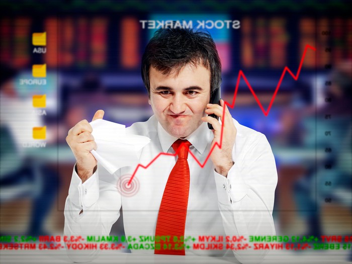 Person angry on the phone as stock portfolio falls