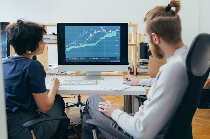 Two colleagues analyzing a financial chart on a computer.