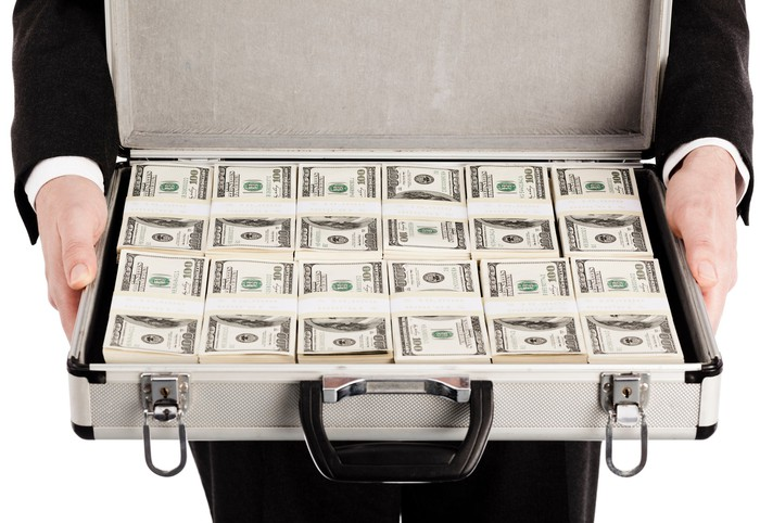 Person holding suitcase with bundles of hundred dollar bills.