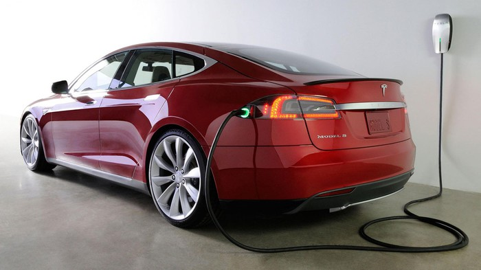 A Tesla Model S plugged into an electric outlet for charging.