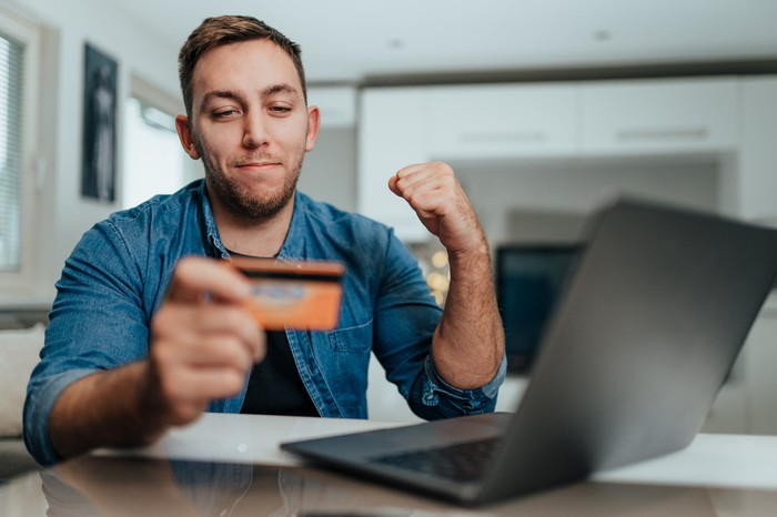 A person at a laptop, holding a credit card and motioning victory with their other arm.