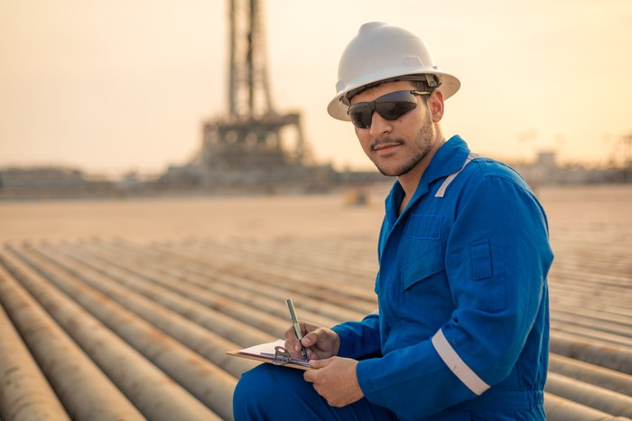 A person in protective gear with pipes and an oil rig in the background.