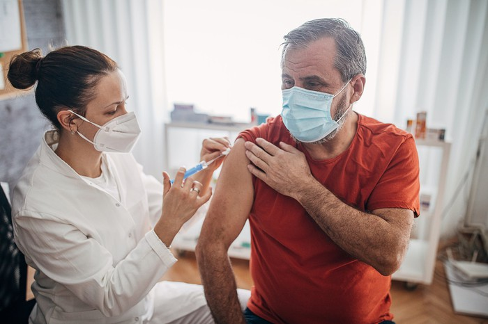 A healthcare worker vaccinates a person in a medical office.