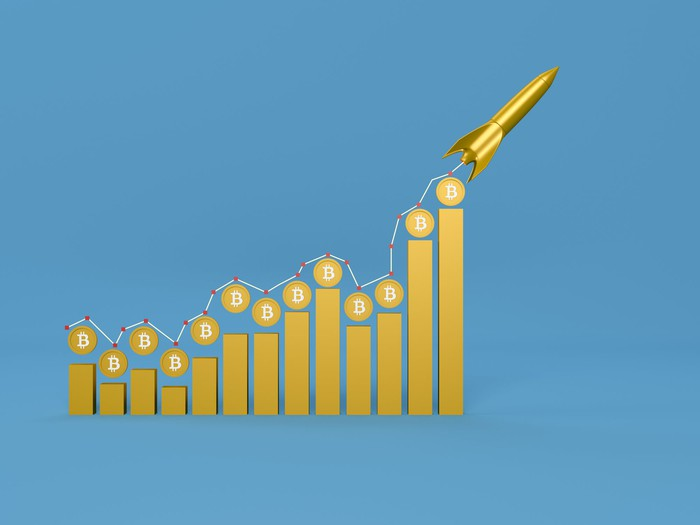 Bitcoin chart with a rocket shooting upwards.