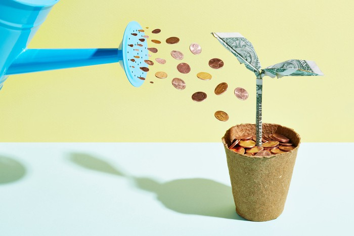 Watering can with coins coming out of it into plant pot filled with coins.