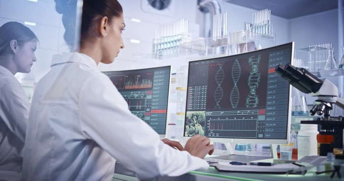 Two scientists in a laboratory look at monitors with images of DNA helices and other genetic data.