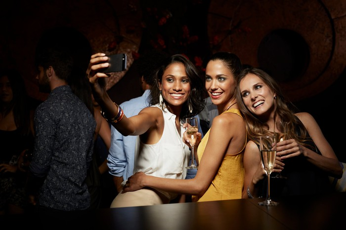 A group of friends at a party taking a selfie.